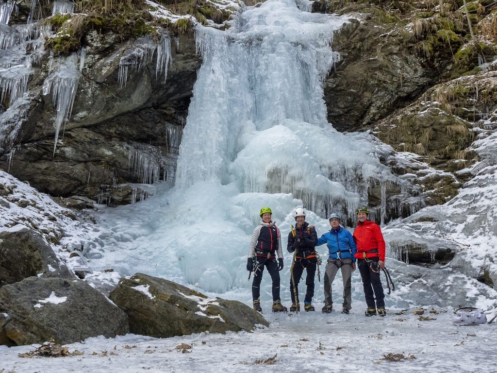 four people standing at bottom of frozen waterfall